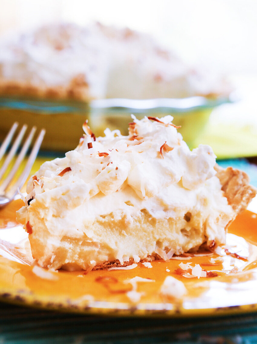Slice of coconut cream pie on a yellow plate with a fork