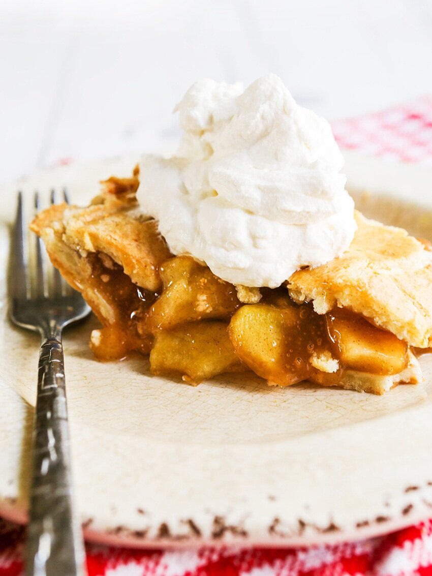 Slice of apple pie with whipped cream on top