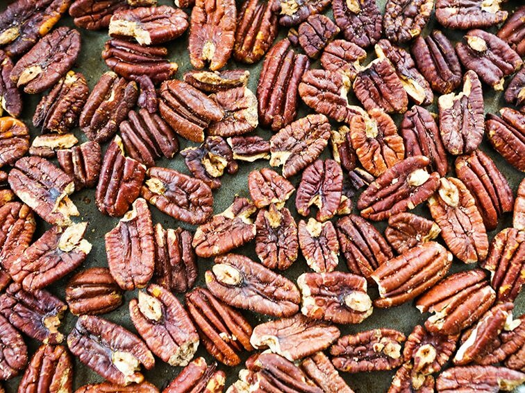 Toasted pecans in a single layer on baking sheet