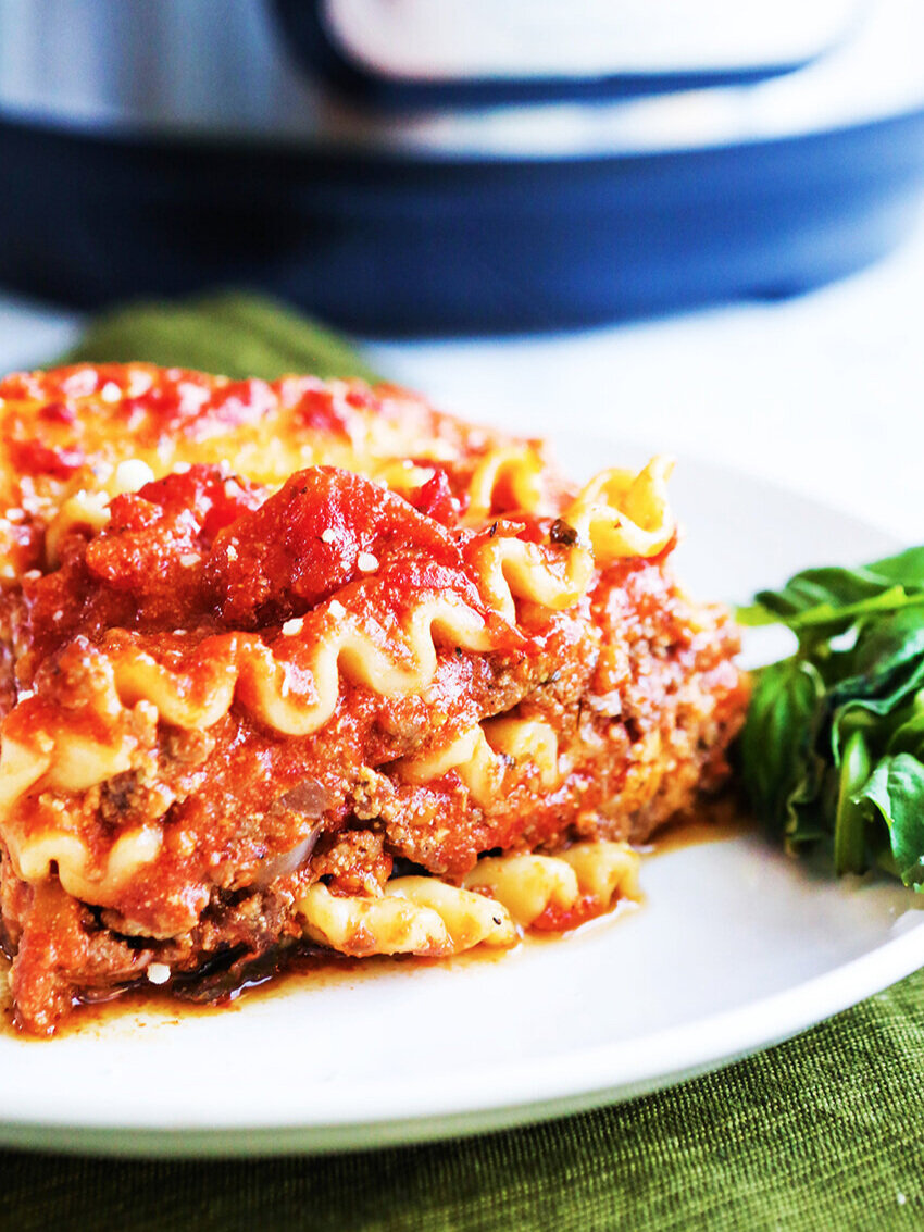 Piece of lasagna on a plate sitting next to Instant Pot