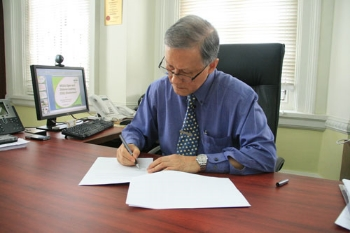 Prof Ho signs the agreement.