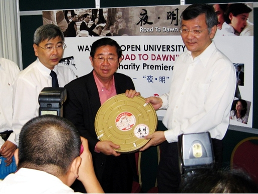 Chia (centre) as Chairman of the Steering Committee for the Charity Premiere, receives the film stock.