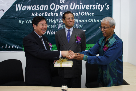 Prof Dhanarajan presents a souvenir to Chia as Abdul Ghani looks on.