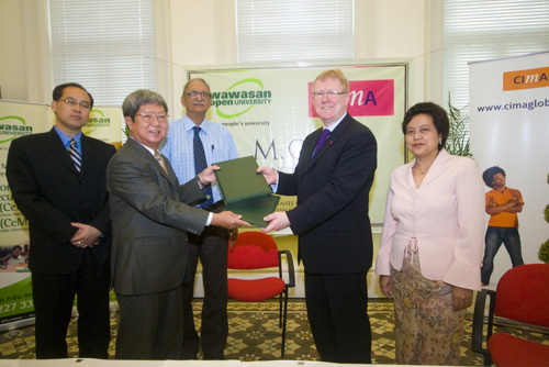 Prof Wong (2nd from left) exchanges the document with Jelly (2nd from right) witnessed by Chet Singh (centre), Dr Seah (left) and Sopiah (right).