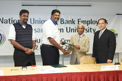 Sivabalan shakes hands with Prof Dhanarajan. Looking on is Solomon (left) and Dr Seah.
