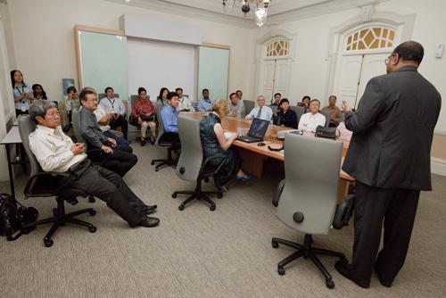 WOU senior management staff listen attentively.