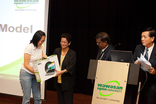 Tan happy to receive the laptop from Prof Mogana while Penang Regional Office director K Manoharan and Marketing & Admissions senior executive Teh Kim Kow (right) look on.