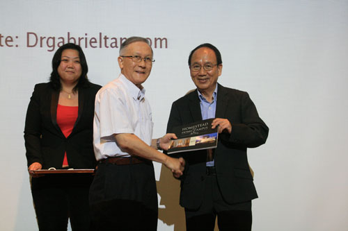 Prof Ho presents the WOU coffee table book to Dr Tan as SFLS lecturer Dr Ooi Chia Yi looks on.