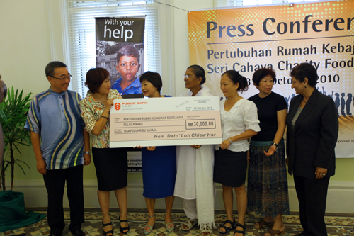 Puan Sri Sue Dhanarajan (centre) receives a mock cheque from Dato' Loh Chiew Hor (left). Datin Irene Martin (2nd from left) is patron of the Home.