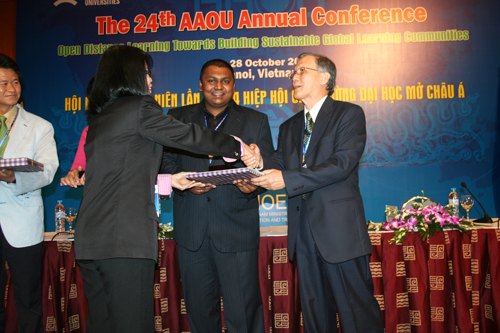 Prof Ho presents a prize as Ishan (centre) looks on.