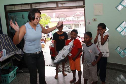 WOU staff Choy Paik Lin teaches the kids to make paper spaceship.