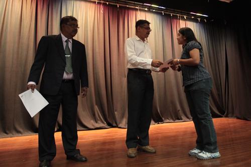 SFLS Acting Dean Dr Nagarajan presents the Dean's List award as Penang Regional Office Director K Manoharan looks on.