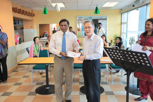 Prof Ho presenting the cheque to Dr Balakrishnan.