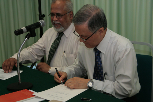 Prof Ho signs the document.