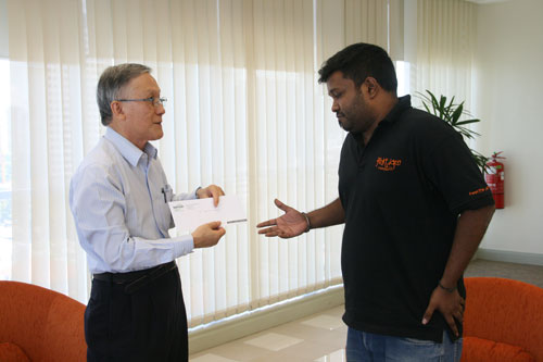 Prof Ho presents the cheque to Sanjeevan.