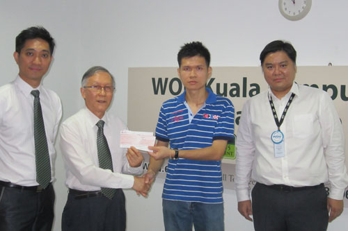 Prof Ho presents cheques to Siong Hon, witnessed by Adrian (left) and Geoffrey.