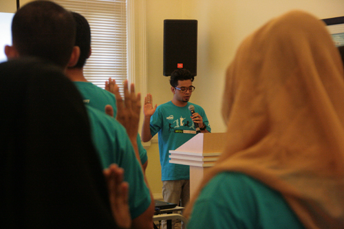 Sharfifi leads in the oath-taking by the new students.