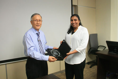 Prof Ho presents a memento of the main campus building to Aishath.