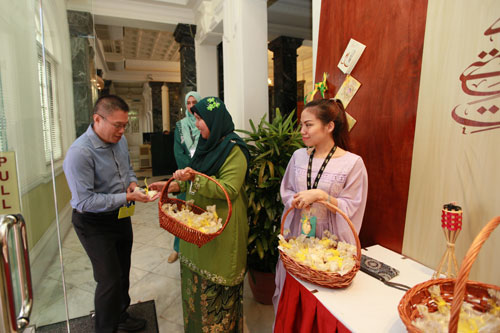 K.H. Chong (left) presented with kuih bangkit. The wooden panel affords an attractive backdrop.