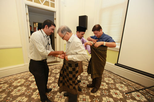 Prof Ho and Yeong (right) learning the art of tying the samping.