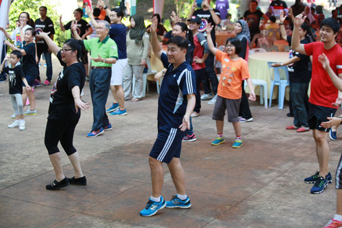Yeong (centre) and Prof Ho (back, in green t-shirt) showing off their zumba moves.