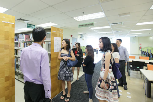 SELC Lecturer Ooi Li Hsien (left) shows the library facilities during the campus tour following the briefing.