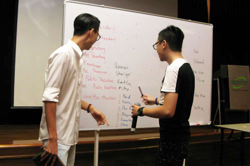 Outgoing president Chow Bai Quan (left) oversees the election process.