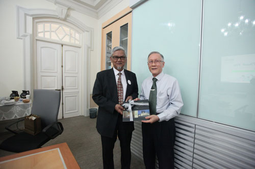Prof Ho (right) presents the University's coffee table book, depicting the Homestead building and the main campus, to Dr Abdul Rahim,