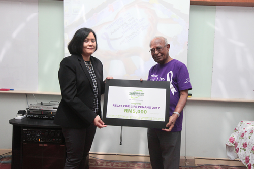 WOU Corporate Communications Manager Rasidah Mion (left) presents the mock cheque to Dato' Seri Dr T Devaraj.