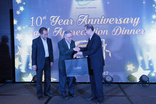 Dr Koh (right) presents a leather briefcase to Prof Ho as Dato' Seri Stephen looks on.