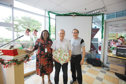 Prof Ho holds the wrapped wooden plaque gift presented by Kevin Tan (right).