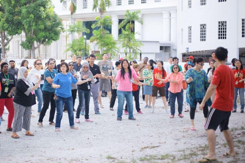 Robin Cheah (foreground, right) leads staff in a few simple zumba dance moves.