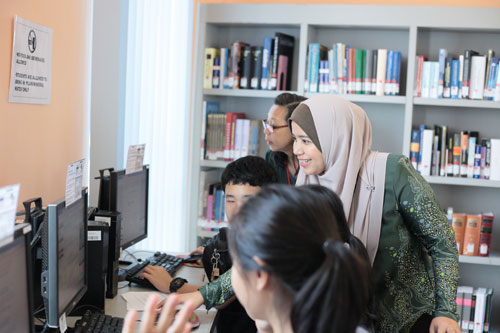 Assistant Library Managers Norhasni and Ooi Siew Lee (back) offer hands-on assistance.