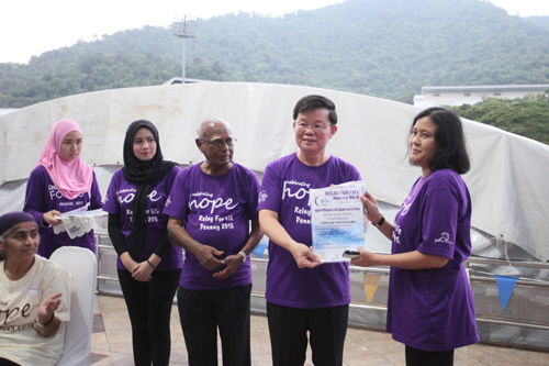 Corporate Communications Manager Rasidah Mion receives the Certificate of Appreciation for the University's sponsorship from the Penang Chief Minister.