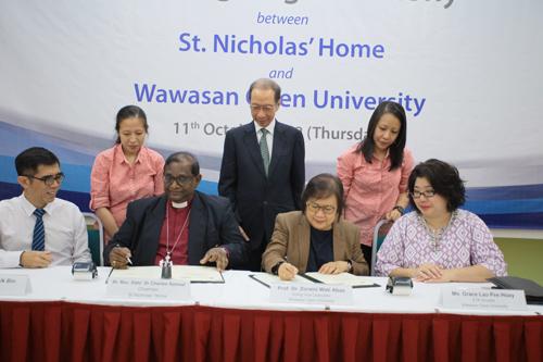 Tan Sri Dr Koh Tsu Koon (standing, centre) witnesses the signing of the Memorandum of Agreement.