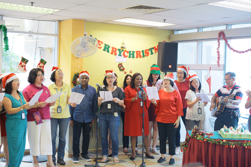 WOU staff sing carols accompanied by guest Michael Gregory (right) on guitar.