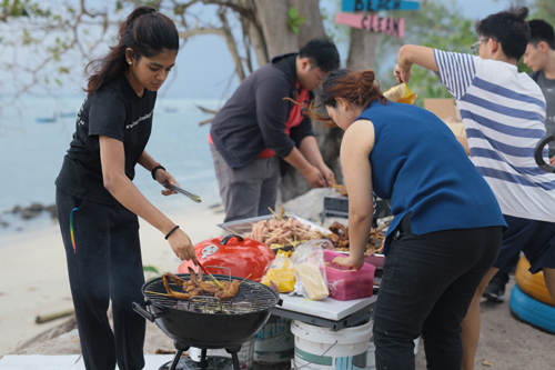 Student Activities Coordinator Khoo Geok Ling (foreground, right) helping the students with the barbeque.