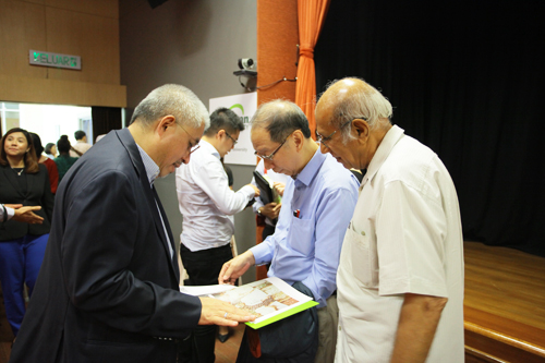 Tan Sri Dr Koh (centre) browses through the book presented to Tan Sri Azman (left) by WOU.