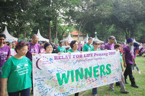 The cancer survivors with the banner that reads 'Winners' and filled with hand-written messages that encourage and inspire.