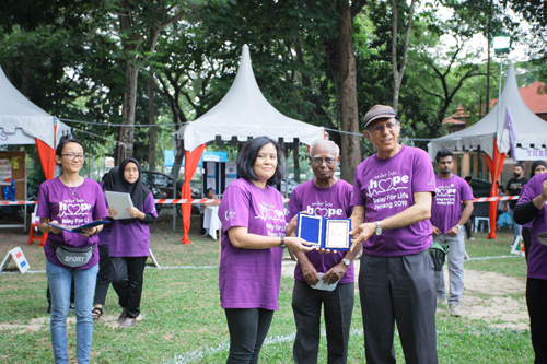 Rasidah receiving a token of appreciation from Dato' Anwar on behalf of WOU.