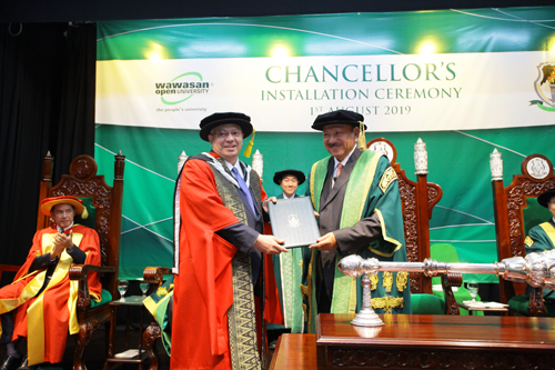 Tan Sri Rashid receives his Honorary Doctor of Business degree as Dato' Seri Stephen Yeap (seated, left) and Registrar Yeong Sik Kheong (background, centre) look on.