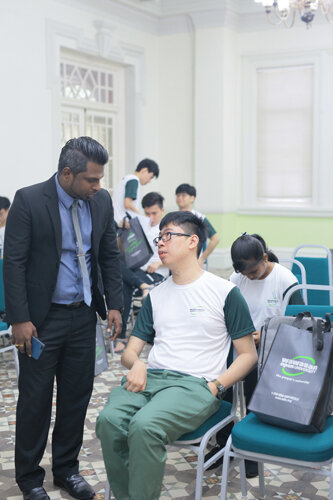 Sasikanth Mariappan (standing) of Penang Regional Centre chats with Pon, who is not allowing his physical disability to disrupt his higher education dreams.