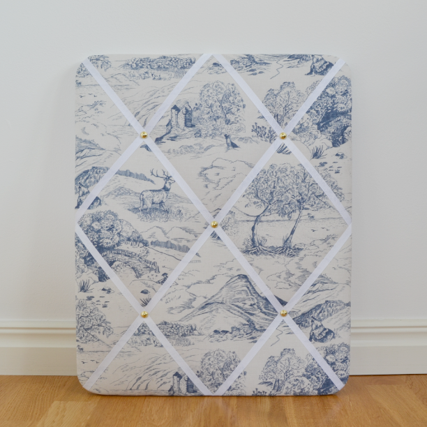 Toile de Jouy pattern with a Scottish theme with motifs of glens, munros, lochs, stags and castle ruins. Dark blue motifs on a textured off-white base. White ribbons. Measures 40x50 cm.