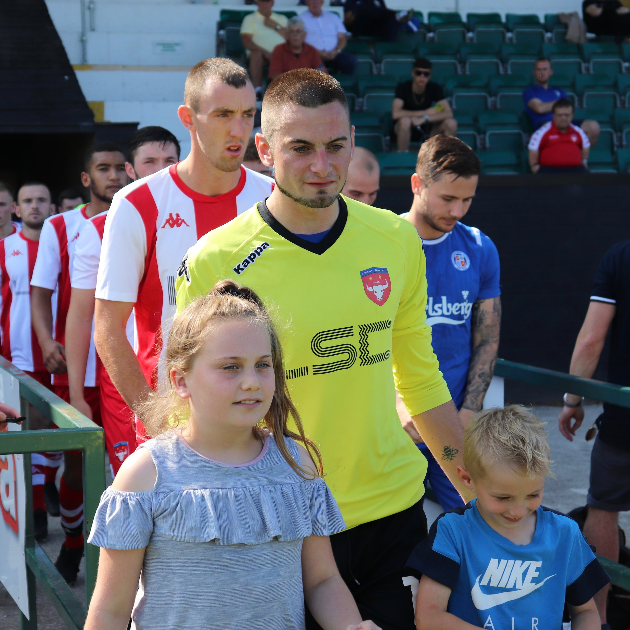 Danny Whiting and our two mascots for the day lead the teams out