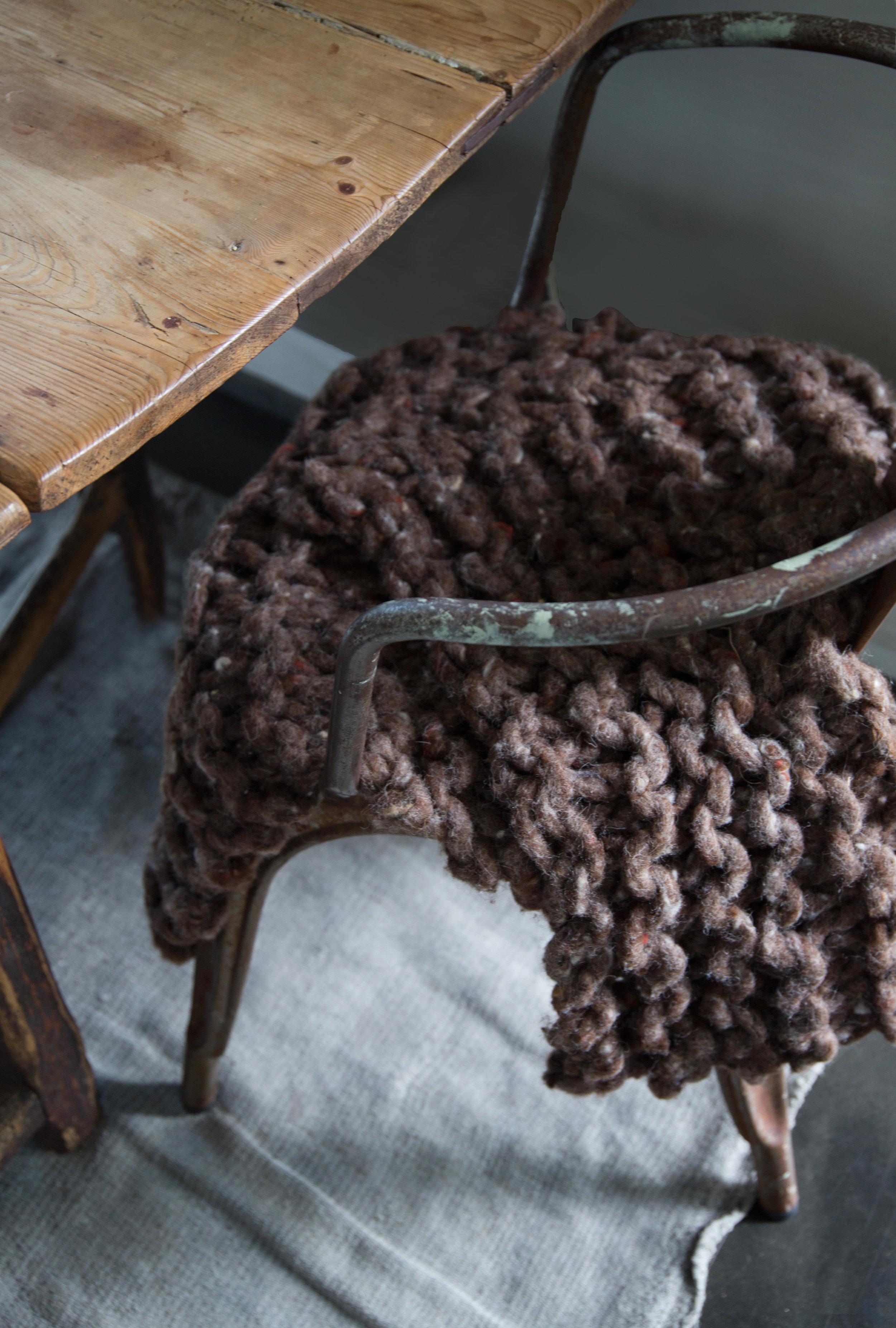"""Harde kalde stoler blir myke og gode å sitte på når du tilfører tekstiler. Det må jo ikke være en pute. Her har jeg strikket et tykt lite """"teppe"""" som gjør den slitte Tolix stolen mer innbydende."""