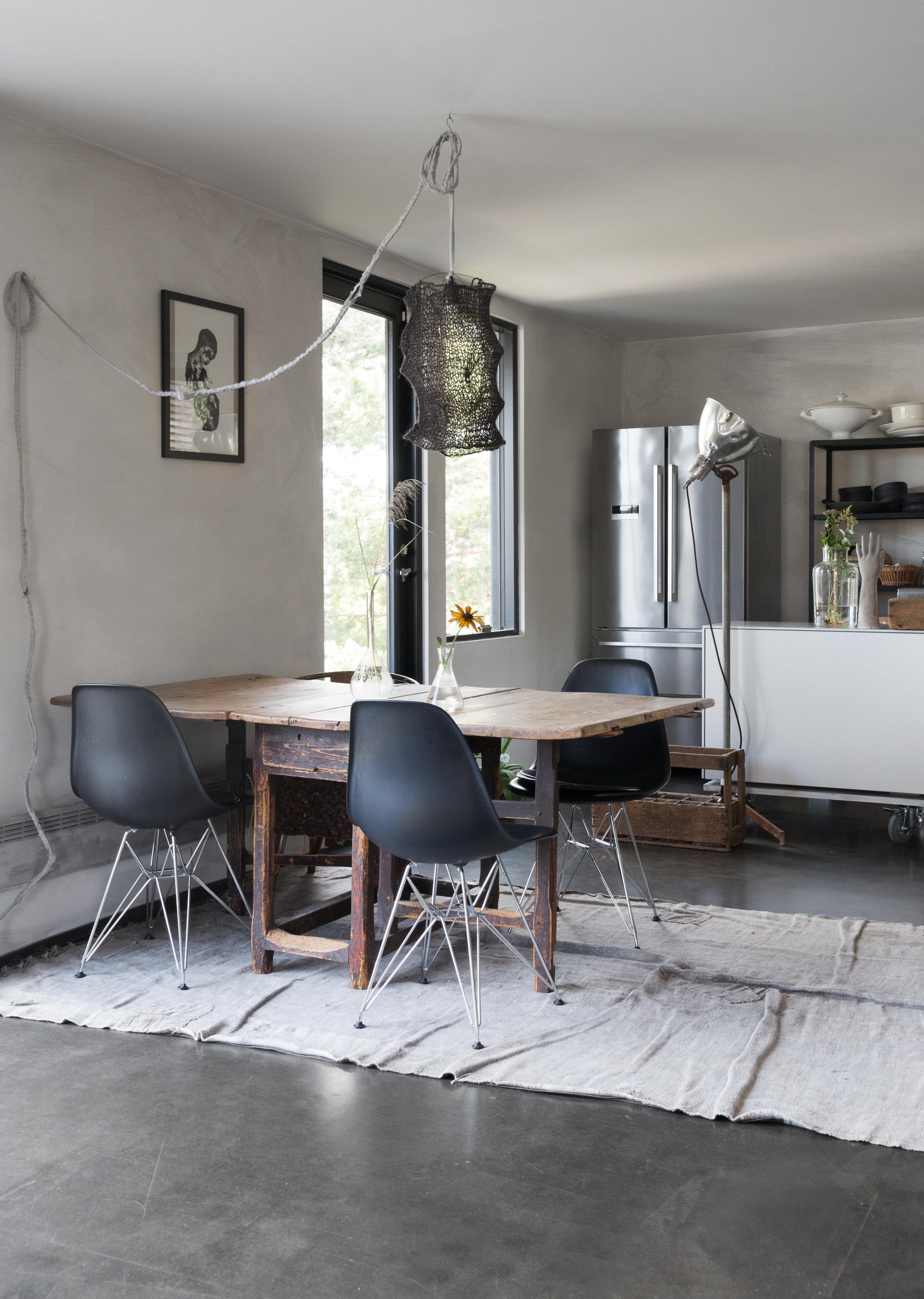Det antikke gamle spisebordet er en fin kontrast til de stramme Eames spisestolene.