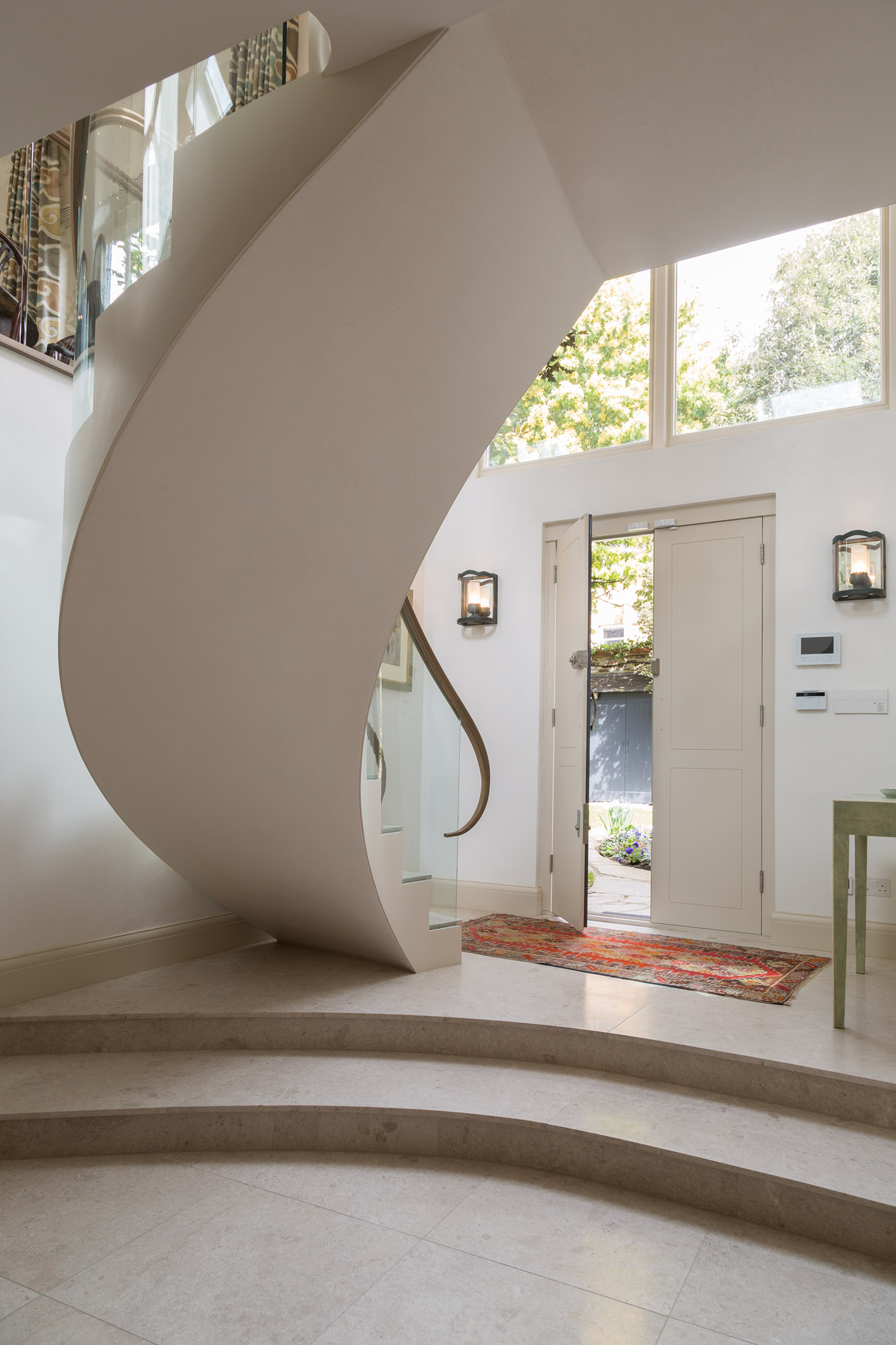 This beautiful staircase sweeps from the entrance hall to the main open plan living space.  Use of wall lighting and table lamps, all connected to the  Lutron  Lighting system make this area feel welcoming at any time of day.