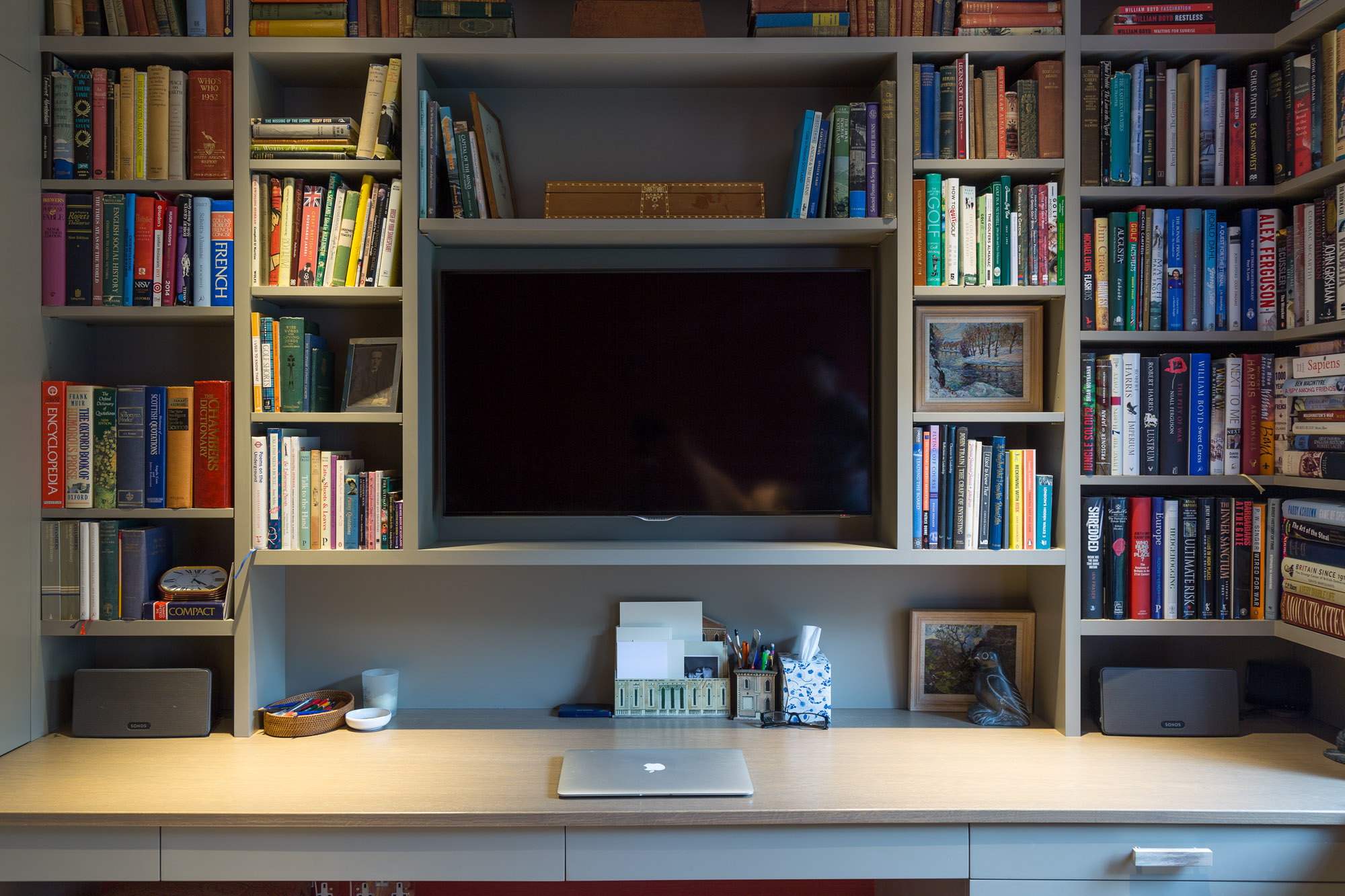 The TV here fits into the decor of the room, allowing the connected video sources from the main equipment rack to be viewed.  Discrete  Sonos  speakers give full stereo sound when working at the desk, or relaxing in the comfy sofa.