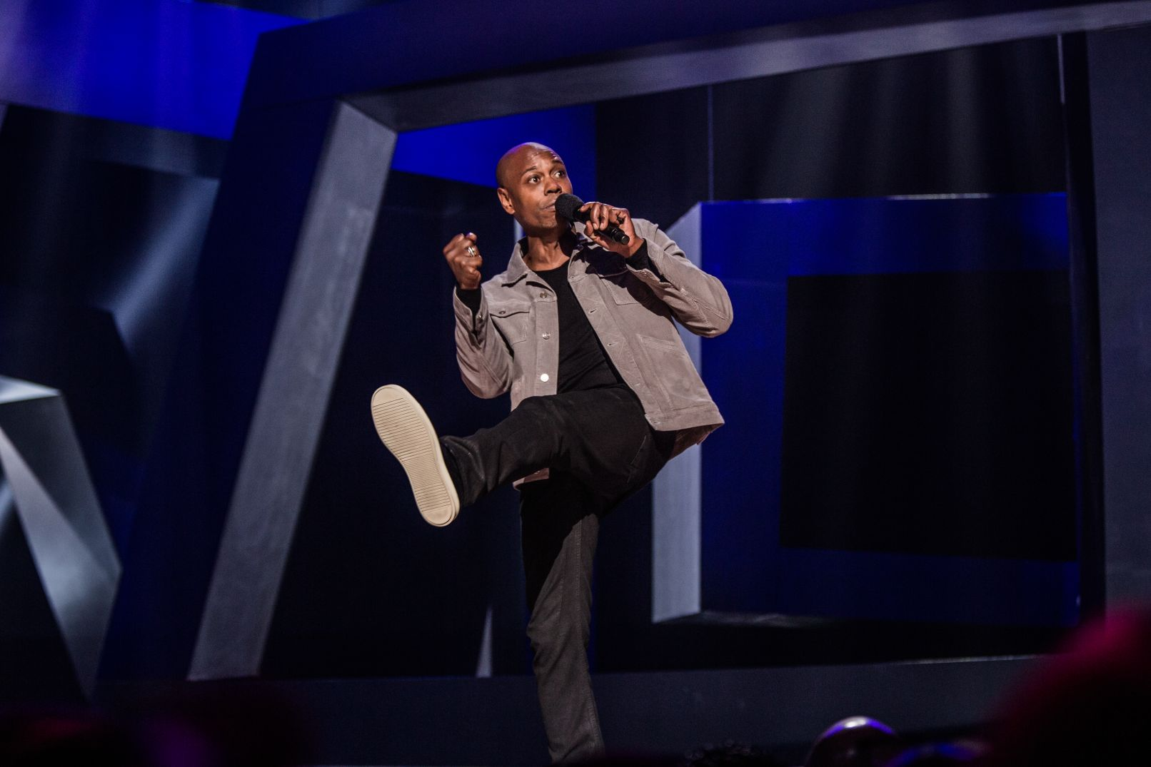 "During his 2017 Netflix special  Equanimity,  Dave Chappelle pantomimes ""kicking her in the pussy"" as he contemplates the woman who lied about Emmett Till. Photo courtesy Netflix."