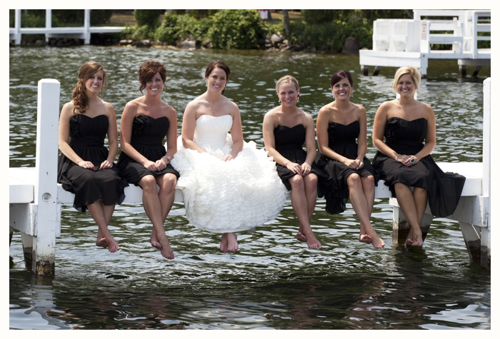 Bridesmaids sitting on a pier